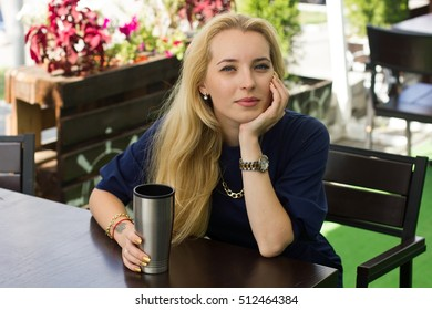 Young blonde woman is sitting in the cafe and drinking coffee