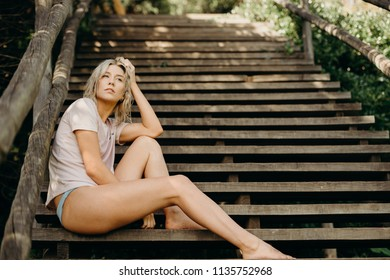 Young blonde woman sitting on wooden stairs at the beach. Summer vibes