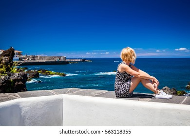 young blonde woman sitting on the stone fence above Atlantic ocean in Puerto de la Cruz, Tenerife, Spain