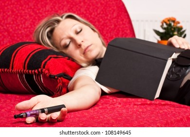 Young blonde woman sleeping while smoking an electrical cigarette