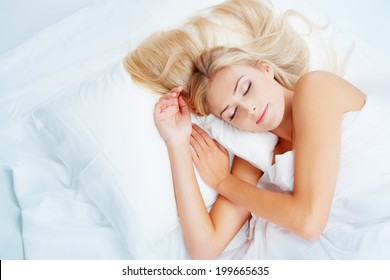 young blonde woman sleeps in white bed