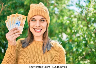 Young blonde woman smiling happy holding swiss franc banknotes at the park.