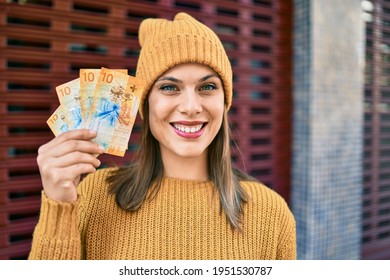 Young blonde woman smiling happy holding swiss franc banknotes at the city.