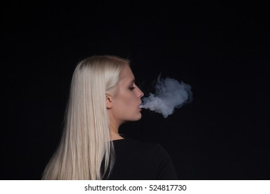 young blonde woman smoking electronic cigarette releasing steam from the mouth