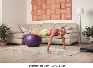 young blonde woman in sportswear doing push-ups on fitness ball indoor at home