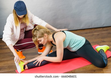 Young blonde woman in sportswear stretching body, working out with her female trainer. Training at home, being fit and healthy.