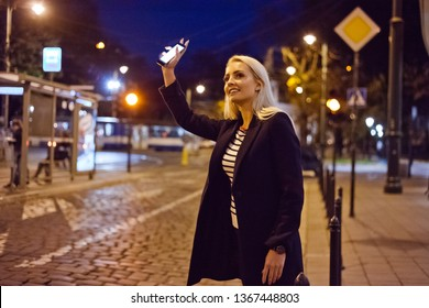Young blonde woman standing in the city street in the evening, holding smart phone in hand and waiting for taxi or uber.