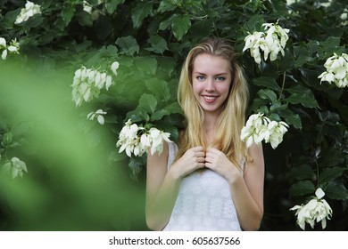 Young blonde woman standing in front of white flowers