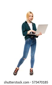 young blonde woman standing and using a laptop, isolated on white background
