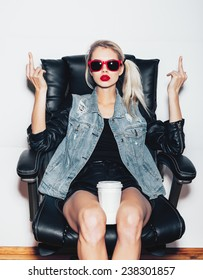 Young blonde woman in sunglasses sit on black office chair and showing middle finger and holding a cup of coffee knees . Fashion hipster girl.  White background, not isolated