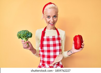 Young blonde woman with tattoo wearing cook apron holding broccoli and red pepper smiling and laughing hard out loud because funny crazy joke.