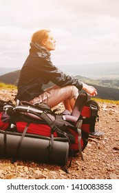 Young blonde woman tourist resting on a hiking backpack in the mountains