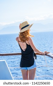 Young blonde woman travelling alone gazing towards the deep blue Aegean sea. Beautiful scenery on a cruise ship during summer period in Cyclades, Greece, Europe.