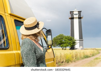 Young blonde woman travelling by yellow camper van though the countryside. Self built off-grid motorhome. Vintage country style.