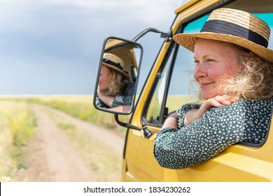 Young blonde woman travelling by yellow camper van though the countryside. Self built off-grid motorhome.