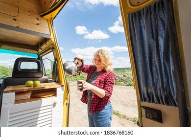 Young blonde woman travelling by camper van though the countryside. Self built off-grid motorhome.