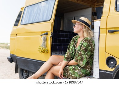 Young blonde woman travelling by camper van at the seaside. Self built off-grid motorhome parked on the beach.