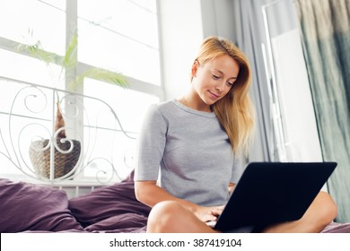 Young blonde woman using laptop on bed