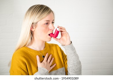 Young blonde woman using a red asthma spray inhaler