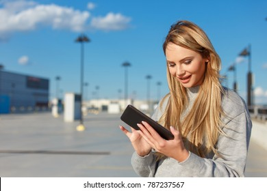 Young blonde woman using tablet outdoors, airport or mall