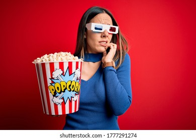 Young blonde woman wearing 3d glasses and eating pack of popcorn watching a movie on cinema looking stressed and nervous with hands on mouth biting nails. Anxiety problem.