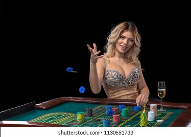 Young blonde woman wearing beautiful sexy shiny dress is playing roulette in the casino