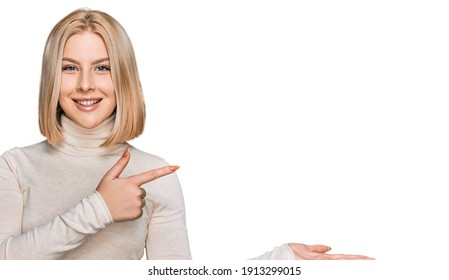 Young blonde woman wearing casual clothes amazed and smiling to the camera while presenting with hand and pointing with finger.