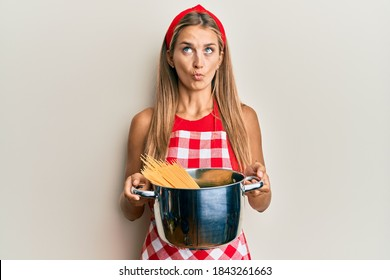 Young blonde woman wearing professional baker apron holding cooking pot with spaghetti making fish face with mouth and squinting eyes, crazy and comical.