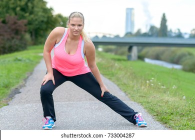 Young blonde woman wearing sportswear stretching outdoors