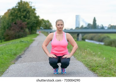 Young blonde woman wearing sportswear practising squats in park near river