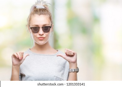 Young blonde woman wearing sunglasses over isolated background looking confident with smile on face, pointing oneself with fingers proud and happy.