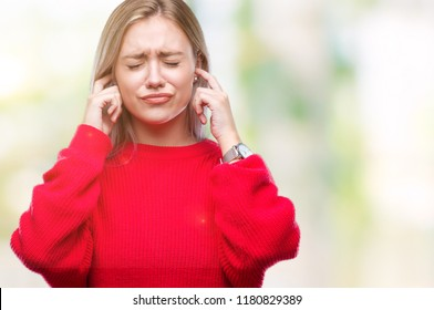 Young blonde woman wearing winter sweater over isolated background covering ears with fingers with annoyed expression for the noise of loud music. Deaf concept.