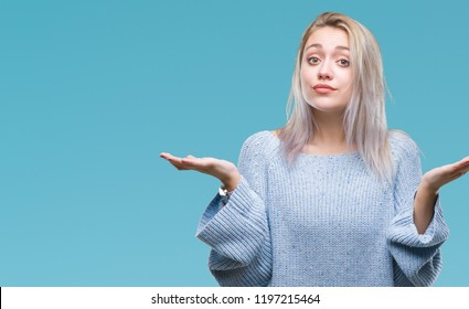 Young blonde woman wearing winter sweater over isolated background clueless and confused expression with arms and hands raised. Doubt concept.