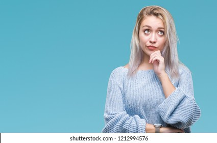 Young blonde woman wearing winter sweater over isolated background with hand on chin thinking about question, pensive expression. Smiling with thoughtful face. Doubt concept.