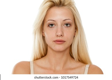 Young blonde woman without makeup on white background