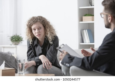 Young, blonde woman with a worried face sitting in a bright psychotherapy office listening to her psychiatrist's advice