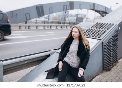 Young blondie caucasian girl coming along metal bridge construction. Architecture, people, city, beauty concept