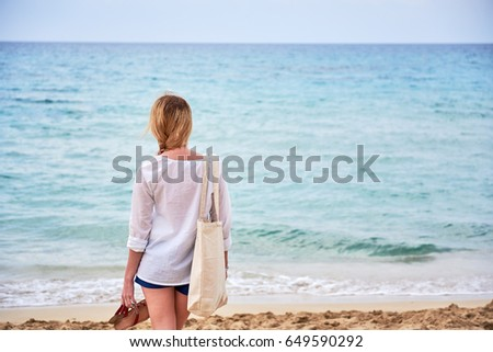 ae38f06e3df1 Young blondie girl walking along coast of sea with her sandals in the hands.