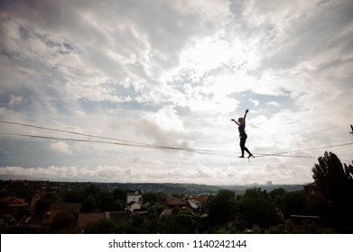 Young blondie woman making steps on the slackline rope on the background of houses among trees and clear sky