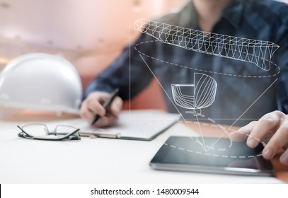 Young blurred sub-designer sitting in the office designing ship for future construction, with digital drawing on tablet PC and paper sketch. Ship design, construction and vessel architecture concept.