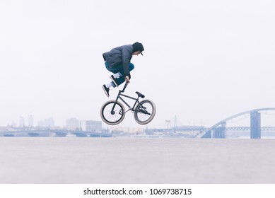 Young BMX bicycle rider does tricks in the air against the background of the urban landscape. BMX freestyle. Street culture