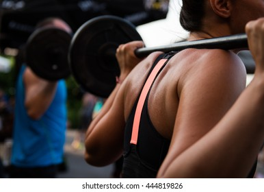 Young body pump woman working out butt exercises, with weights on her back.