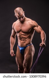young bodybuider training with rubber strip