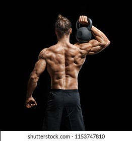 Young bodybuilder doing exercise with kettlebell. Rear view of muscular male with perfect physique on black background. Strength and motivation.