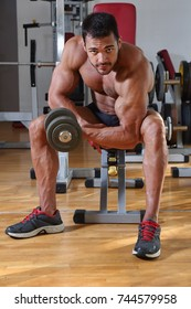 Young bodybuilder exercising in fitness center