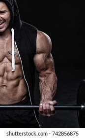 Young bodybuilder exercising in front of black background