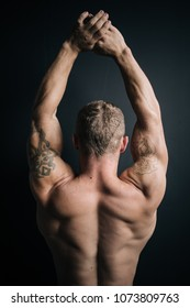 young bodybuilder guy shows wide strong back after exercise and diet. parts of bodies: a man's ass and powerful shoulders. street style in clothes: wide gray jeans. shoulder tattoo