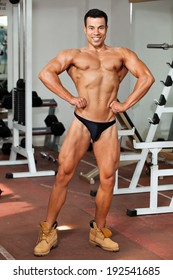 young bodybuilder in the gym, posing, front lat spread