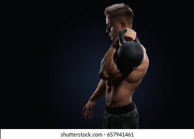 Young bodybuilder holding a kettle bell Strong fitness male exercising crossfit with kettlebell in gym