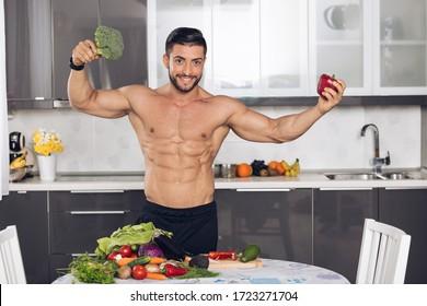 Junge Bodybuilder in der Küche, die eine vegetarische Mahlzeit zubereitet. Fit Mann zu Hause Kochen Gemüse, Früchte im Hintergrund.